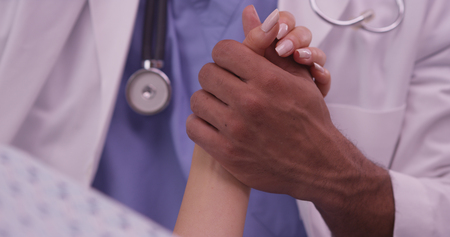 patients: Black doctor holding patients hand