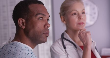 Caucasian woman: Woman doctor talking about xrays to black patient Stock Photo