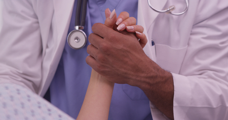 patients: Closeup of African doctor holding patients hand Stock Photo