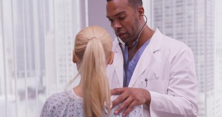 Negro médico escucha el corazón del paciente Foto de archivo