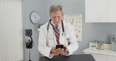 Senior doctor using smartphone in the office