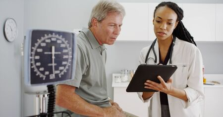 Negro médico de la mujer hablando con el paciente mayor en la oficina