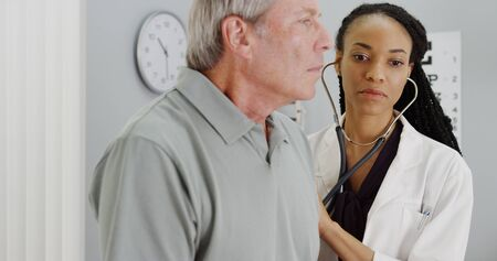 medical exam: African woman doctor listening to elderly patient breathing Stock Photo