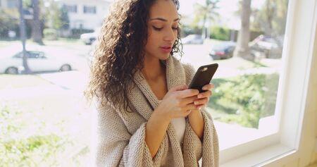 hispanic woman: Beautiful hispanic woman texting on a cell phone.