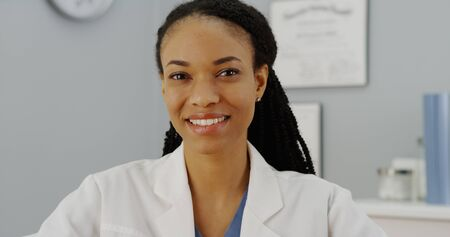 knowledgeable: African woman doctor sitting at desk smiling