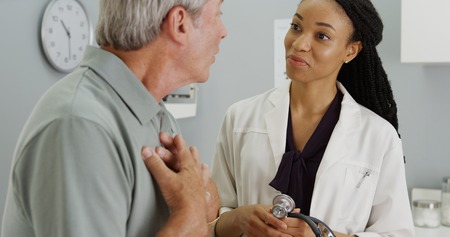 happy young woman: Black woman doctor listening to elderly patient breathing Stock Photo
