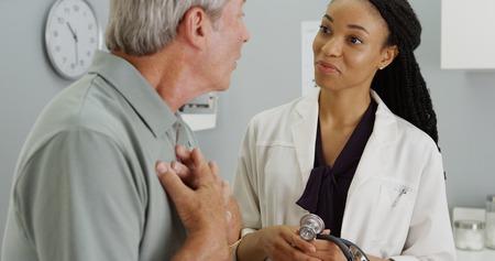 Zwarte vrouw arts luistert naar oudere patiënt ademhaling