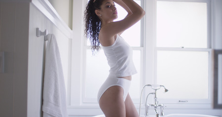 Elegant young mixedrace woman wearing undergarments.