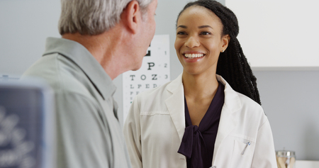 Black woman doctor talking and being positive with senior