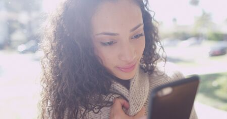 Cute young latino woman looking at a cell phone device.