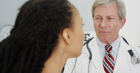 senior adult woman: Senior doctor talking to adult woman in the office