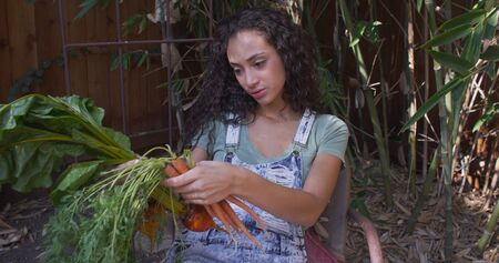 Young hispanic woman smelling and looking at vegetables.