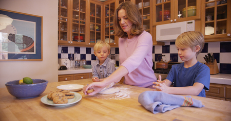 beautiful boys: Beautiful white mother preparing cookie dough with her boys. Stock Photo