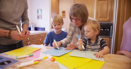 Senior grandma teaching grandchildren to draw.