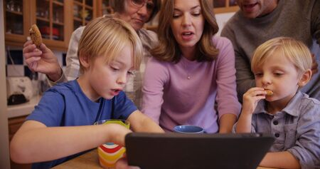 indulging: Closeup of a beautiful caucasian famly enjoying cookies while watching an ebook.