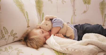 adorable child: Closeup of an adorable sleepy young child lying on a sofa.
