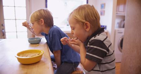 comiendo cereal: Poco muchacho joven que come el cereal con su hermano. Foto de archivo