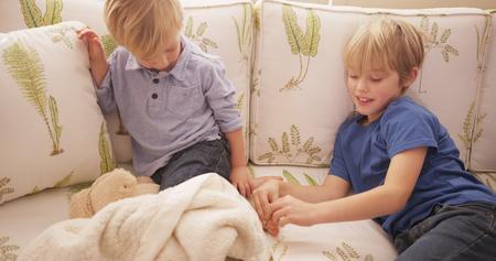 Giovane ragazzo biondo solletica i piedi di suo fratello su un divano. Archivio Fotografico - 53155052