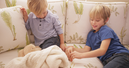 tickling: Young blond boy tickling his brothers feet on a sofa.