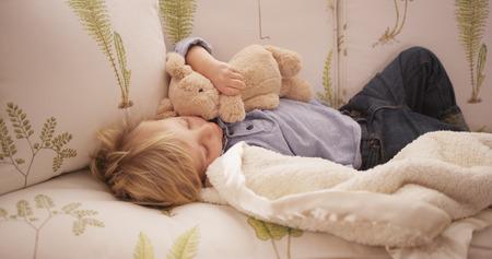 stuffed toys: Cute little white boy lying on a sofa.