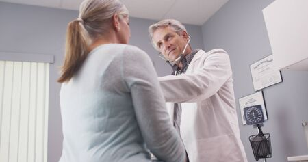 Doctor examining patient with stethoscope.