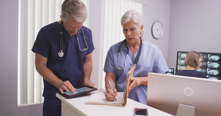 elderly patient: Beautiful mature nurse writing notes in patient file with male colleague. Stock Photo