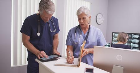 enfermera con paciente: Madura hermosa enfermera escribir notas en el archivo del paciente con el colega masculino.