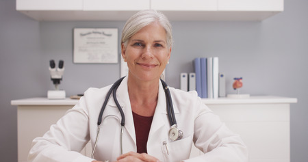 Smiling attractive mature female doctor talking to camera patient POV. Stok Fotoğraf