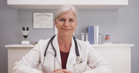Smiling attractive mature female doctor talking to camera patient POV. Archivio Fotografico