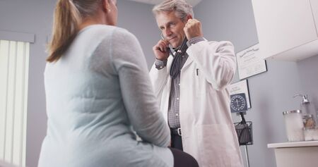 vitals: Male senior doctor listening to patient vitals with stethoscope.