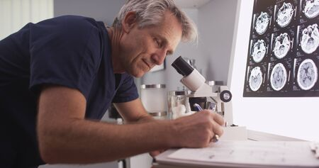 radiologist: Middle aged male radiologist looking through microscope