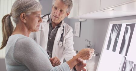 huesos: médico de sexo masculino mayor evaluación de fractura en la muñeca del paciente. Foto de archivo