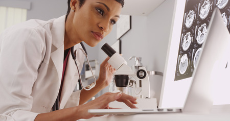 x ray equipment: Female technician looking in a microscope