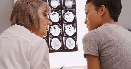 cerebro blanco y negro: Superior de mujeres médico revisar la radiografía resultados con el paciente