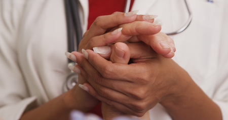 Close up of doctors hands holding patients hand