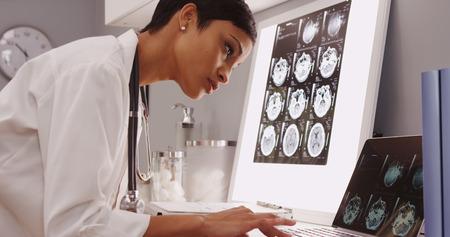 asistente médico de sexo femenino joven que mira exploraciones de rayos x