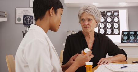 Young intelligent female doctor prescribing medication to patient