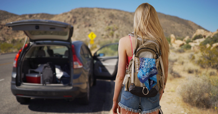 intelligent: Young attractive woman comes across abandoned vehicle in the desert.
