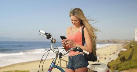 wait: Lovely young California woman at beach texting bicycle owner to pick up his bike.
