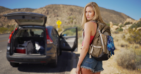 shrubbery: Young attractive woman abandons vehicle in the desert to steal a new ride. Stock Photo