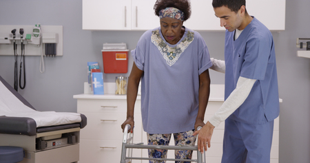 Young male nurse helps senior black woman walk with crutches