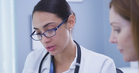 Close up of young attractive hispanic medical doctor talking with senior patient