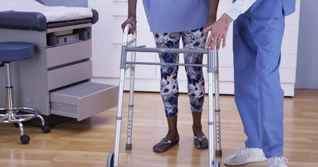 Portrait of senior black woman walking with crutches indoors medical clinic