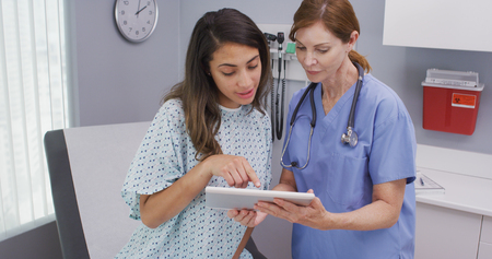 Closeup of senior nurse using tablet computer to share test results with patient