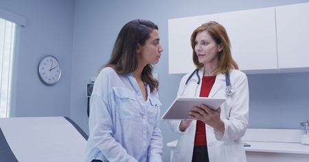 Close-up van arts die high-tech tablet gebruikt om gezondheidsgeschiedenis met patiënt te herzien