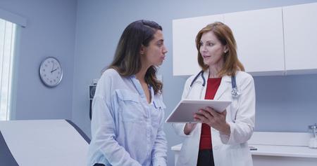 Primo piano del medico che utilizza tablet ad alta tecnologia per rivedere la storia sanitaria con il paziente