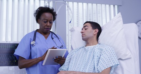 Mid aged African nurse checking on male patient with electronic notebook tablet Zdjęcie Seryjne