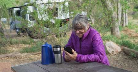 Active senior woman resting on park bench texting on smart phone in nature.