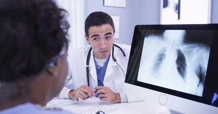 Close up of male doctor showing patient an x-ray of her lungs on computer Archivio Fotografico