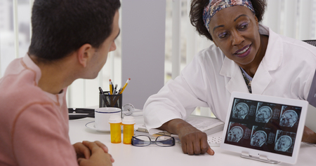 Middle aged black doctor talking with patient about ct-scans and medication Foto de archivo - 110930504